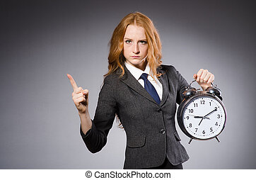 Young nice businesswoman with alarm clock pointing