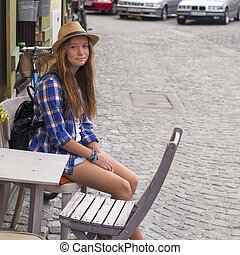 Young nice girl sitting at an outdoor cafe in the old town. European Tour.