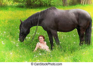 Young nude woman with horse enjoying the country air