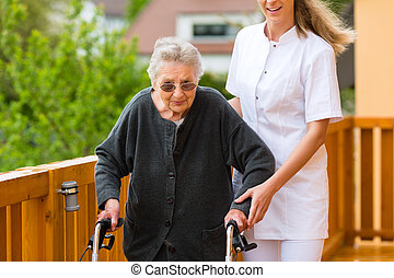Young nurse and female senior with walking frame, the...