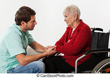 Young nurse full of compassion assisting lady on wheelchair