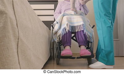 Young nurse caring of elder disabled woman in wheelchair
