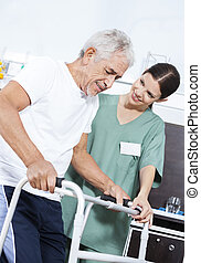 Young Nurse Helping Patient In Using Walker At Rehab Center