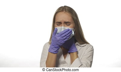 Young nurse in medical mask on white background in robe looks directly into camera. With one hand holds his throat and coughs. She is sick and sad. High quality 4k footage