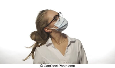 Young nurse in robe, medical mask with glasses on white background removes one hand dressed in medical glove hair clip. High quality 4k footage