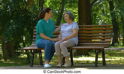 Young nurse spending sunny day with senior woman in park