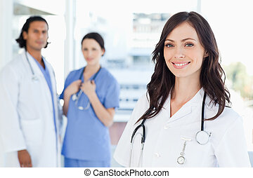 Young nurse standing in front of two colleagues