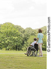 Young nurse with senior woman in middle of the garden -...