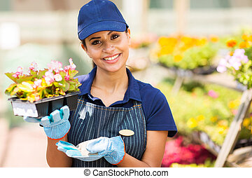young nursery worker in greenhouse