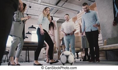 Young office employees play with football during break. Casual workers enjoy healthy workplace atmosphere slow motion.