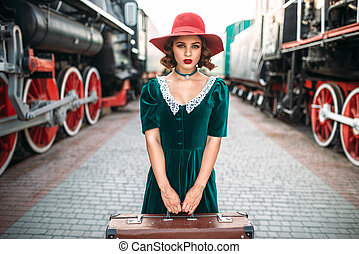 Young old-fashioned woman travels on retro train