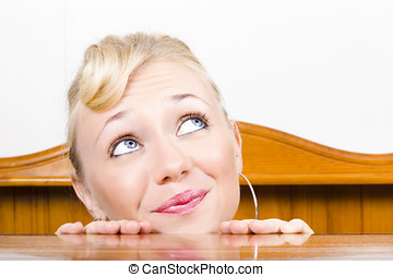 Young, optimistic Caucasian woman stares upwards from behind a countertop.