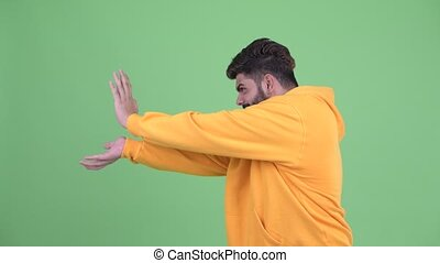 Young overweight bearded Indian man with super power gesture...