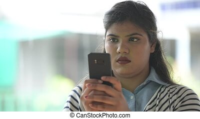 Young overweight beautiful Indian businesswoman in the streets outdoors