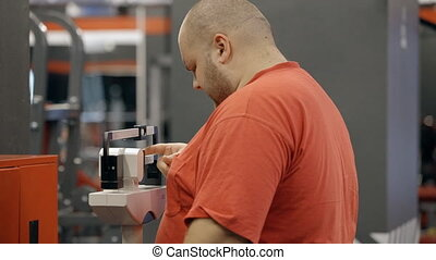 Young overweight man standing in gym on mechanical scale
