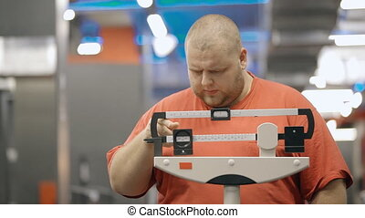Young overweight man standing in gym on mechanical scale -...