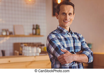 Young owner posing in his cafe with arms crossed