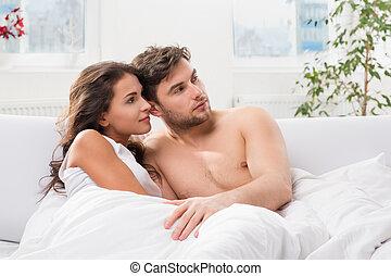 young párosít, elterül in ágy, karóra televízió