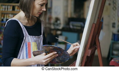 Young painter girl in apron painting still life picture on canvas in art-class