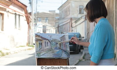 Young painter painting cityscape with watercolor