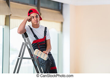 Young painter painting the ceiling in construction concept