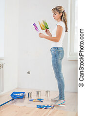 young painter standing in room holding two color palettes and lo