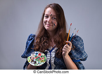 Young painter with palette and paintbrushes