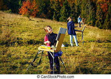 Young painters at work near waterfall - Group of young ...