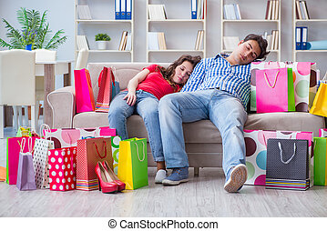 Young pair after shopping with many bags