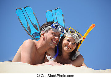 young pair in fins and underwater masks lies on sand