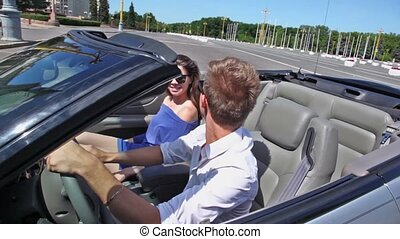 Young pair ride backward in cabriolet on street at sunny day