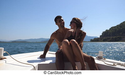 Young pair sitting on bow of boat and posing to photographer...
