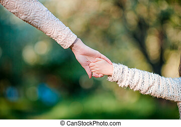 Young parent holds the hand of a small kid