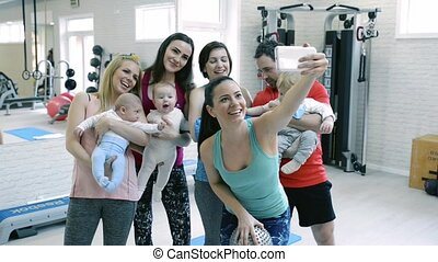 Young parents and babies in modern gym taking selfie.