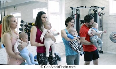 Young parents and babies in modern gym with personal trainer.