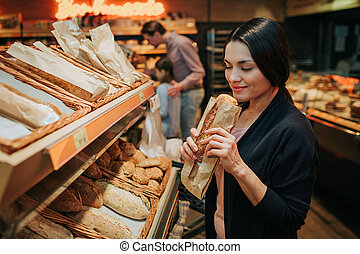 Young parents and daughter in grocery store. Cheerful woman smell bread she hold in hands. Father stand behind with daughter and carry grocery trolley.