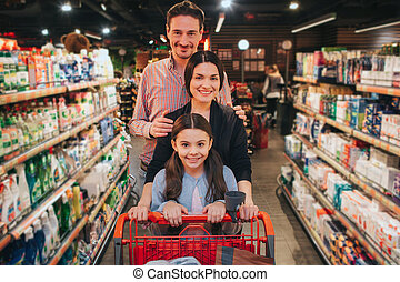 Young parents and daughter in grocery store. They walk among...