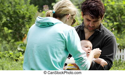 Young parents feeding a baby boy outdoor