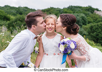 Young parents in wedding dresses kiss their young daughter in cheeks