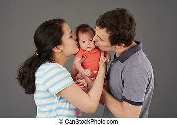 Young parents kiss small baby
