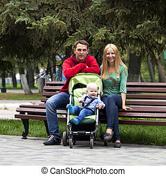 Young parents sit on a bench with his young son