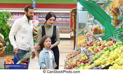 Young parents with a little daughter choose fresh apples in a large supermarket.