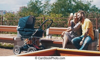 Young parents with baby carriage on bench. Take selfie on smartphone. Family.