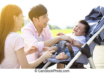 young parents with baby crying in the carriage