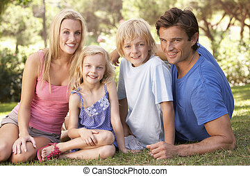 Young parents with children posing in a park