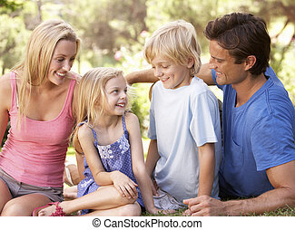 Young parents with children talking in a park