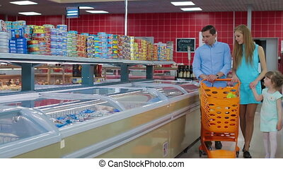 Young parents with little daughter choose food in a large supermarket. man chooses frozen fish in grocery store supermarket sale, shopping marketplace food with grocery trolley