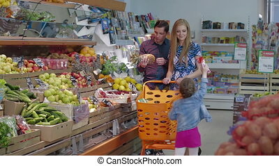 Young couple choose fresh fruits in a large supermarket. Man selecting fresh ananas in grocery store supermarket sale, shopping marketplace food with grocery trolley