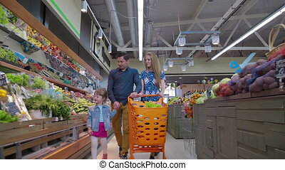 Young couple choose fresh fruits in a large supermarket. Man selecting fresh ananas in grocery store supermarket sale, shopping marketplace food with grocery trolley.