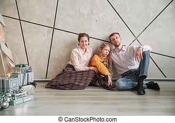parents with their little daughter sitting on the floor in a new apartment
